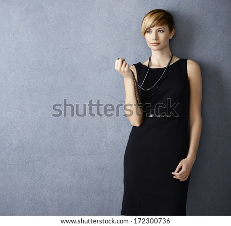 Attractive young woman wearing black dress and pearl necklace on grey background - stock photo