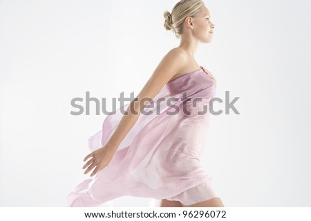 Attractive young woman wearing floaty pink silk fabric.