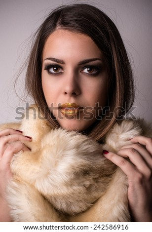 Attractive young woman wearing furry winter fashion snuggling down into the softness and warmth of the fur while looking at the camera with parted lips - stock photo
