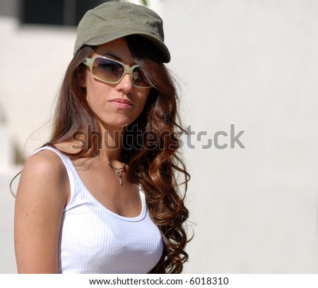 Attractive young woman wearing hat and sunglasses. Space for text. - stock photo