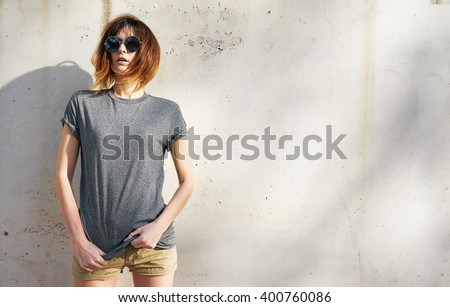attractive young woman wearing in a gray blank t-shirt posing on a background of a concrete wall in the rays of the setting sun - stock photo