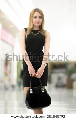 Attractive young woman wearing little black dress holding suede handbag in modern building - stock photo