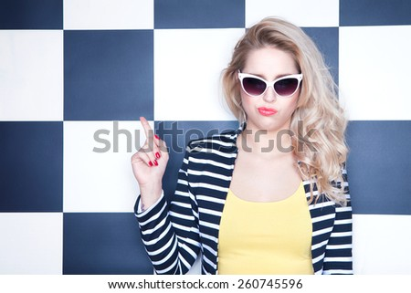 Attractive young woman wearing sunglasses on checkered background, pointing up, beauty and fashion concept - stock photo