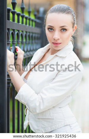 Attractive young woman wearing white jacket posing near metal fence - stock photo