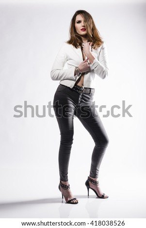 Attractive young woman wearing white leather jacket over her bra und standing in jeans and sandals isolated against white background.