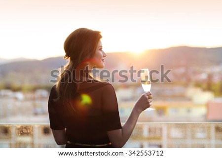 Attractive young woman with a drink on a terrace of a bar - stock photo