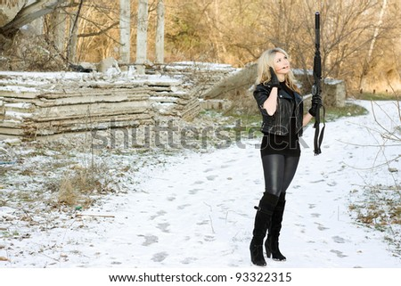Attractive young woman with a gun outdoors - stock photo