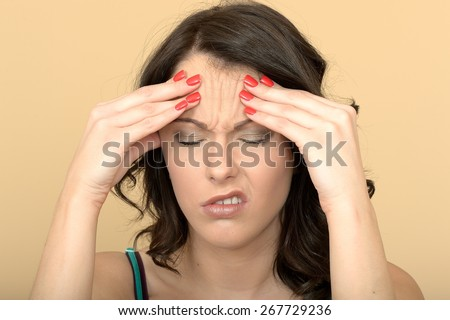 Attractive Young Woman With a Painful Headache Holding Her Head - stock photo