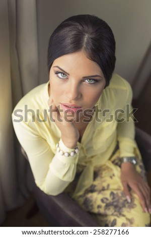 Attractive young woman with a perfect skin and gorgeous green eyes looking at the camera seductively - stock photo