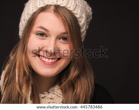 Attractive young woman with a wool cap on a dark background - stock photo