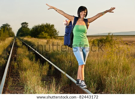Attractive young woman with backpack walking along the rail - stock photo