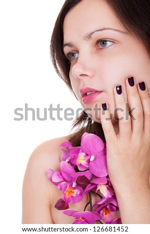 Attractive young woman with beautiful manicured nails holding a spray of pink orchids up to her chin - stock photo