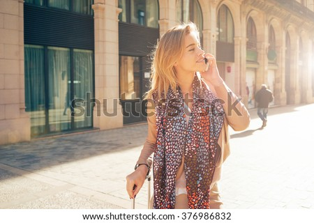 attractive young woman with blonde hair messaging talking on the smart-phone at the city street background. pretty girl talking on the phone in the glow the setting sun - stock photo