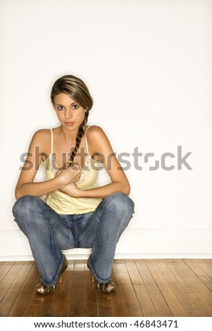 Attractive young woman with braided hair smiling and squatting with her back to the wall. Vertical shot. - stock photo