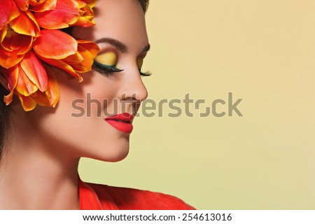 Attractive young woman with bright make-up and flowers on her head - stock photo