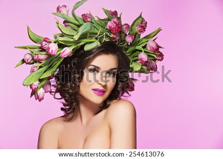 Attractive young woman with bright make-up and flowers on her head over pink background - stock photo