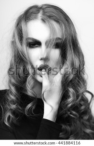 attractive young woman with bright makeup on pretty sexy face and blonde curly long hair holding finger in mouth, black and white
