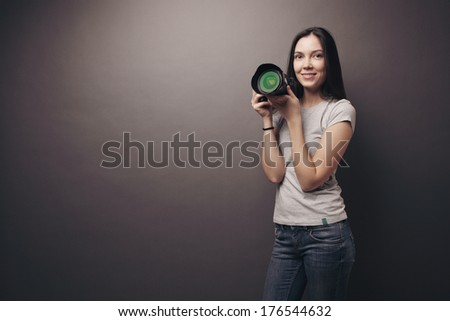 Attractive young woman with camera - stock photo