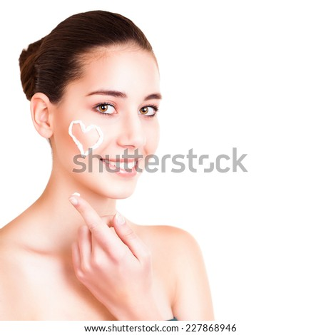 attractive young woman with creme forming a heart - stock photo