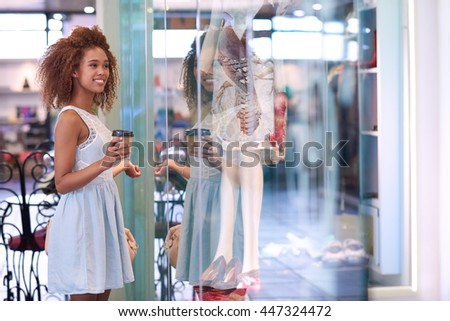 Attractive young woman with curly hair smiling and drinking a coffee looking through a store window while enjoying a day shopping in a mall - stock photo
