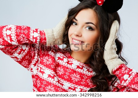Attractive young woman, with curly hair, wearing in red Christmas sweater and gloves, posing with hands on head, on the white background, in studio, close up - stock photo