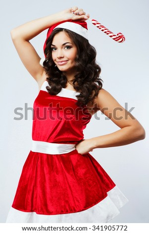 Attractive young woman, with curly hair, wearing in red santa costume, holding colorful candy in her hand, on the white background, in studio, waist up - stock photo