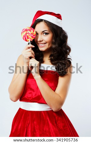 Attractive young woman, with curly hair, wearing in red santa costume, posing with colorful candy near her face, on the white background, in studio, waist up - stock photo
