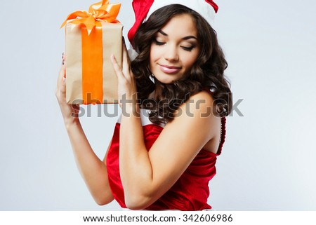Attractive young woman, with dark curly hair, wearing in red santa costume, holding present in her hands, on the white background, in studio, waist up - stock photo