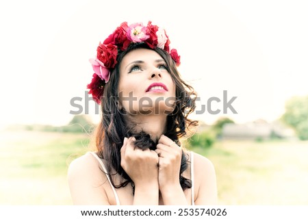 Attractive young woman with floral wreath on her head with sunset in background. Shallow DOF. Vintage stylized. - stock photo