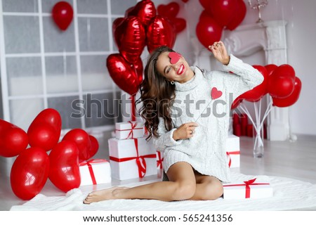 Attractive young woman with gifts and balloons