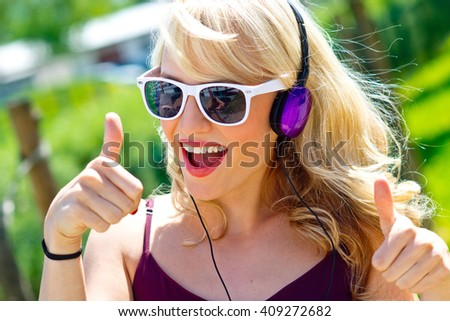 attractive young woman with headphones listen music outdoor