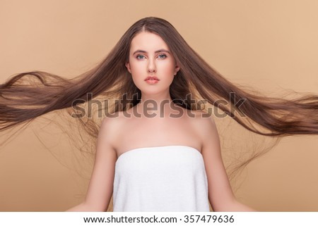 Attractive young woman with her long hair blowing. She is standing and looking forward with passion. Isolated on brown background - stock photo