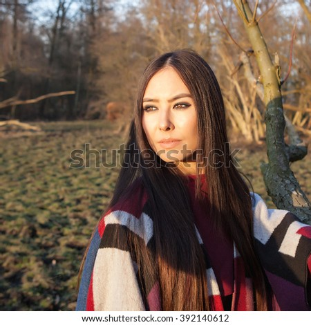 Attractive young woman with long beautiful hairs posing in park at sun set.