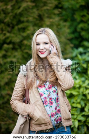 Attractive young woman with long blond hair in a trendy jacket standing in a park or garden talking outdoors on her mobile phone with a friendly smile - stock photo