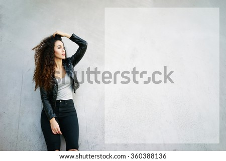 Attractive young woman with long curly hair standing against street wall background and looking at the copy space area for your text message or information - stock photo
