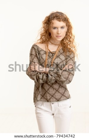 Attractive young woman with long curly hair standing with arms crossed. - stock photo