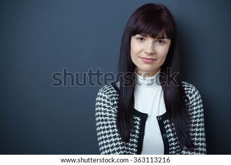 Attractive young woman with long dark brown hair and a pensive expression posing against a dark background with copy space, head and shoulders view - stock photo