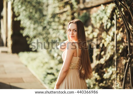 Attractive young woman with long dress enjoying her time outside in park sunset background - stock photo