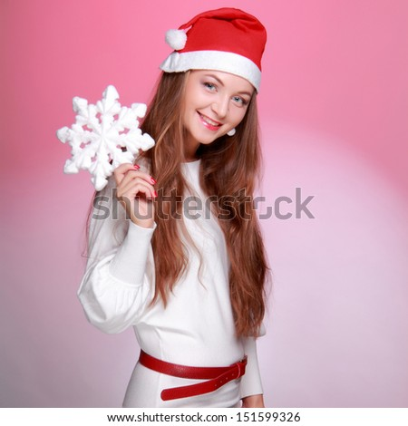 Attractive young woman with long hair holding a Christmas snowflake on Holiday