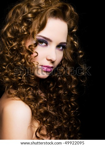 Attractive young  woman with  long ringlet hairs - isolated on black - stock photo
