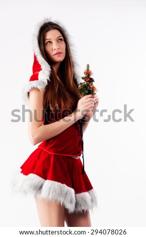 Attractive young woman with New Year tree in Santa costume. - stock photo