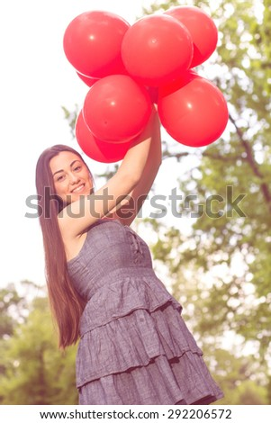 Attractive Young Woman with Red Balloons at Beautiful Summer Day Outdoor. Happy female enjoying nature. - stock photo