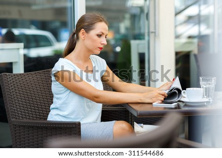 Attractive young woman with red lips reads a newspaper sitting in a cafe - stock photo