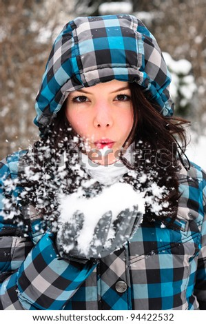 Attractive young woman with snow in her hand - stock photo