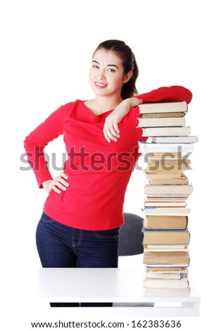 Attractive young woman with stack of books. Isolated on white.
