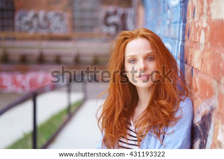 Attractive young woman with tousled red hair leaning against an exterior brick wall with graffiti looking at the camera with a quiet smile - stock photo