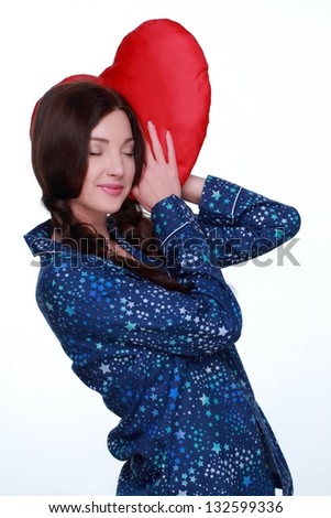 Attractive young woman with two braids in her pajamas holding a big red heart om white background