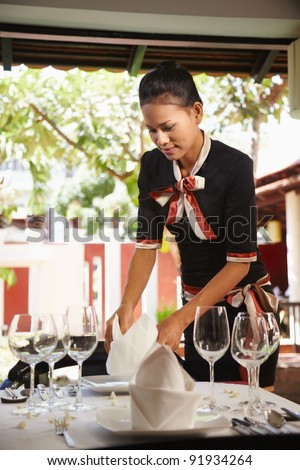 Attractive young woman working as waitress in exclusive restaurant, setting up a table. Waist up, side view - stock photo
