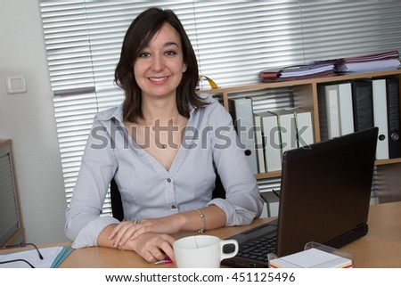 Attractive young woman working at the desk smiling - stock photo