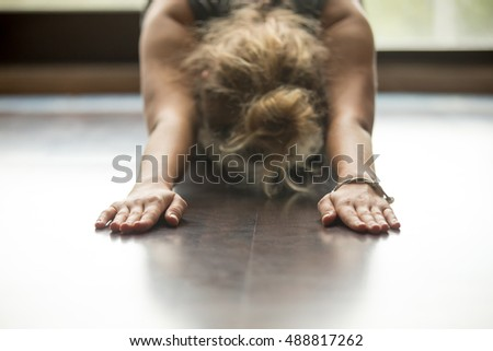 Attractive young woman working out at home, doing yoga exercise on blue mat, lying in Balasana, Child Pose, Ardha-Kurmasana (Half Tortoise Pose). Close-up, focus on hands